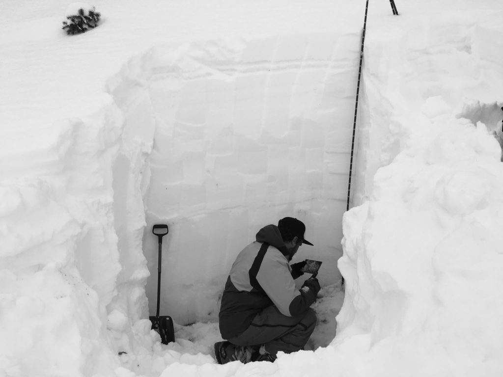 Digging for snow pits to test stability for avalanche.